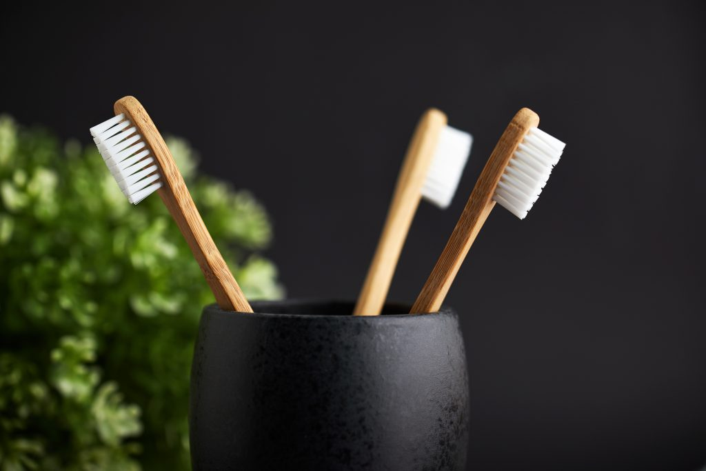 three toothbrushes in a cup